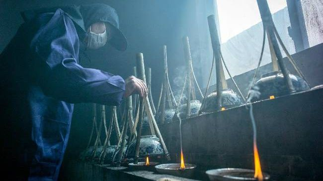craftsperson in overalls and face mask lifting ceramic bowl with bamboo conical handle off oil lamp in ink making workshop anhui china