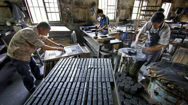 three craftspeople making ink sticks in huimo workshop anhui china left arranging sticks on drying tray back pushing dough into moulds right beating dough front tray of ink sticks