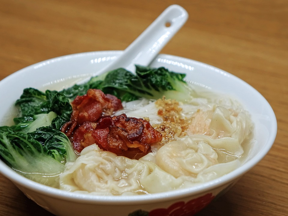 bowl of wonton soup with meat and green vegetable