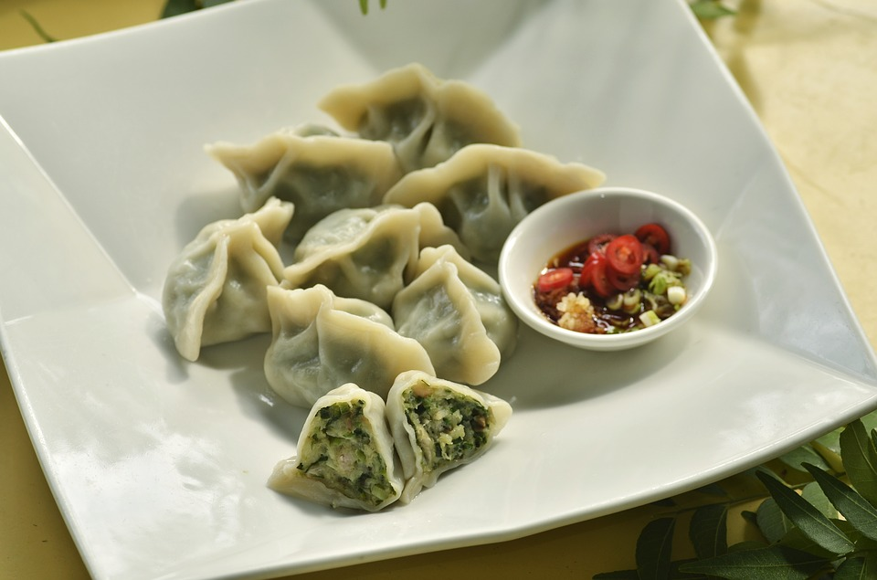 shui jiao dumplings with egg and chive filling and bowl of sauce