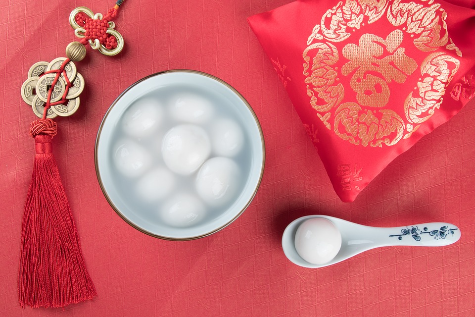 bowl of tangyuan chinese dumpling soup with spoon and red new year decorations