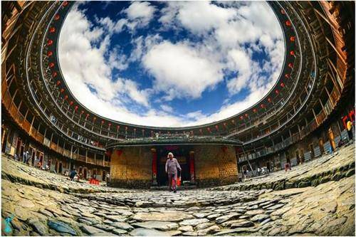 person walking across cobbled inner courtyard of tulou fisheye lens photo