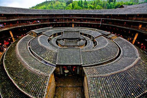 concentric round tiled roof buildings inside courtyard of larger circular tulou building in fujian china