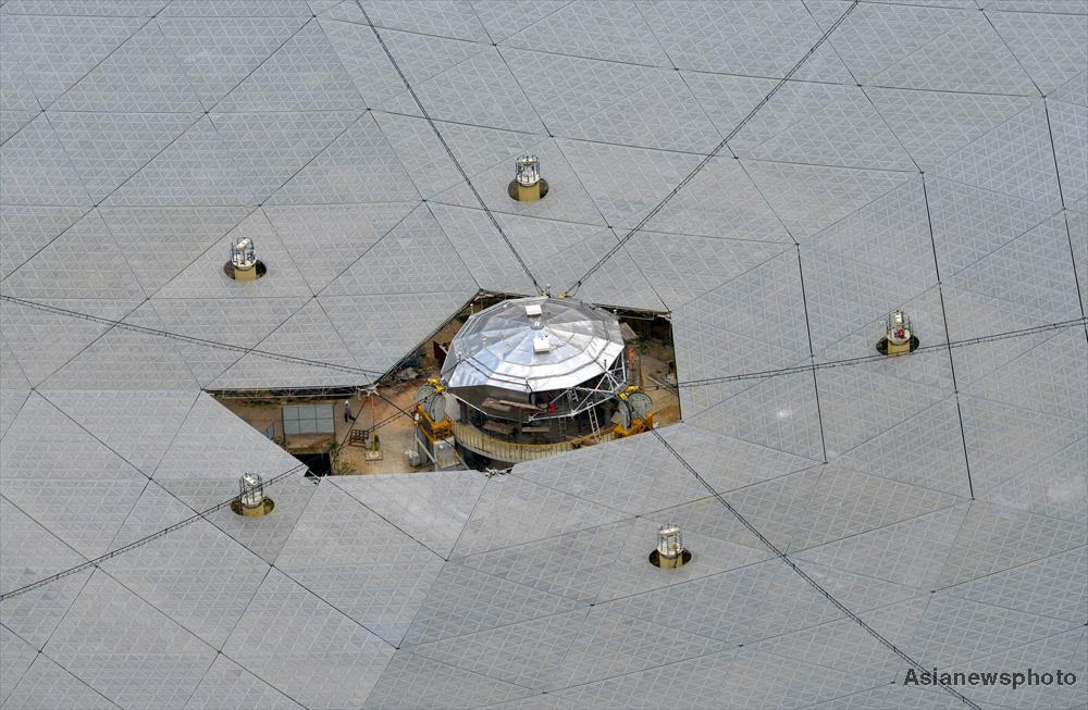 Fitting the final panels on China's 500 metre diameter FAST radio telescope.