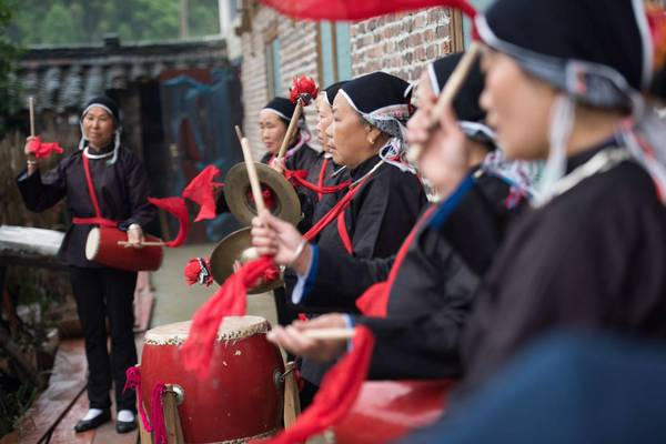 people in dark blue traditional dress playing drums