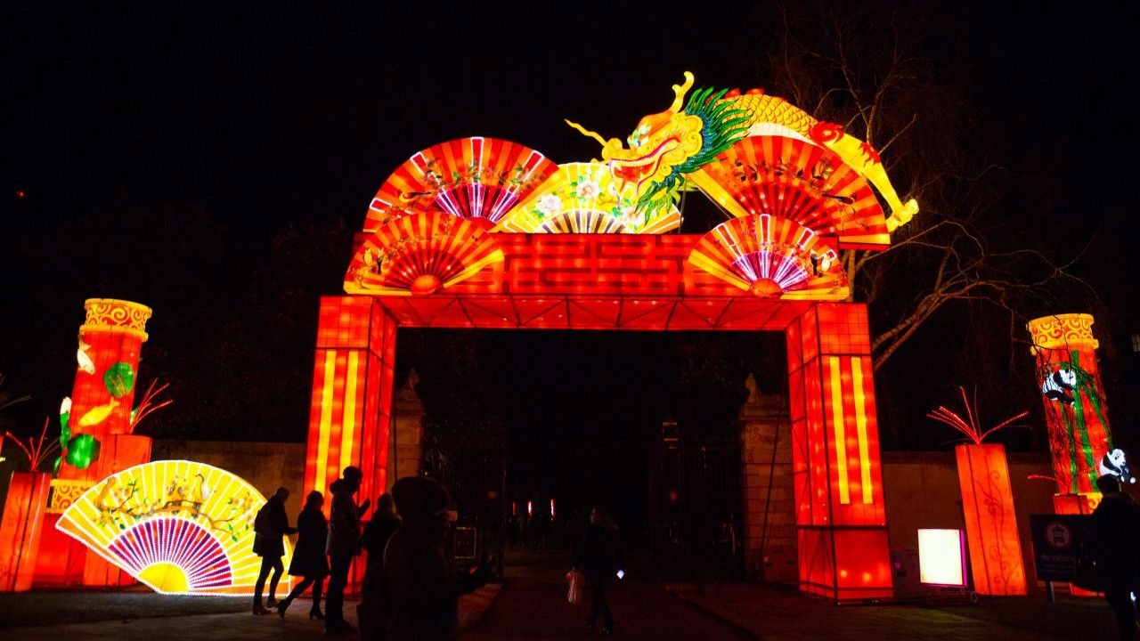 A park at night with a giant illuminated archway lantern structure complemented by dragon and fan decorations.
