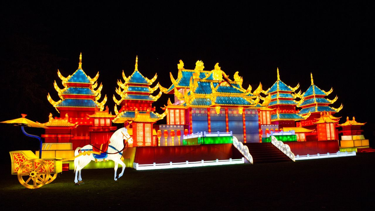 A park at night with an illuminated lantern display of a colourful Chinese imperial palace with a white horse outside.