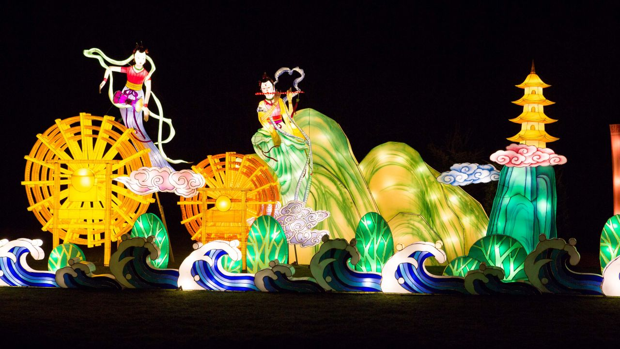 a park at night with giant illuminated lanterns depicting a scene of waves, clouds, hills, water mills and a flautist and drummer flying through the air