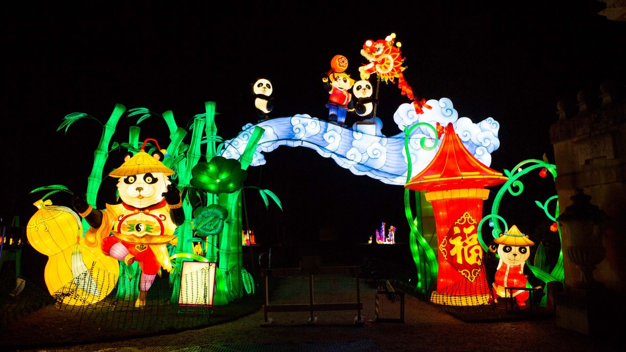 a park at night with a giant lantern display showing cartoon pandas, bamboo, goldfish and ceremonial decorations