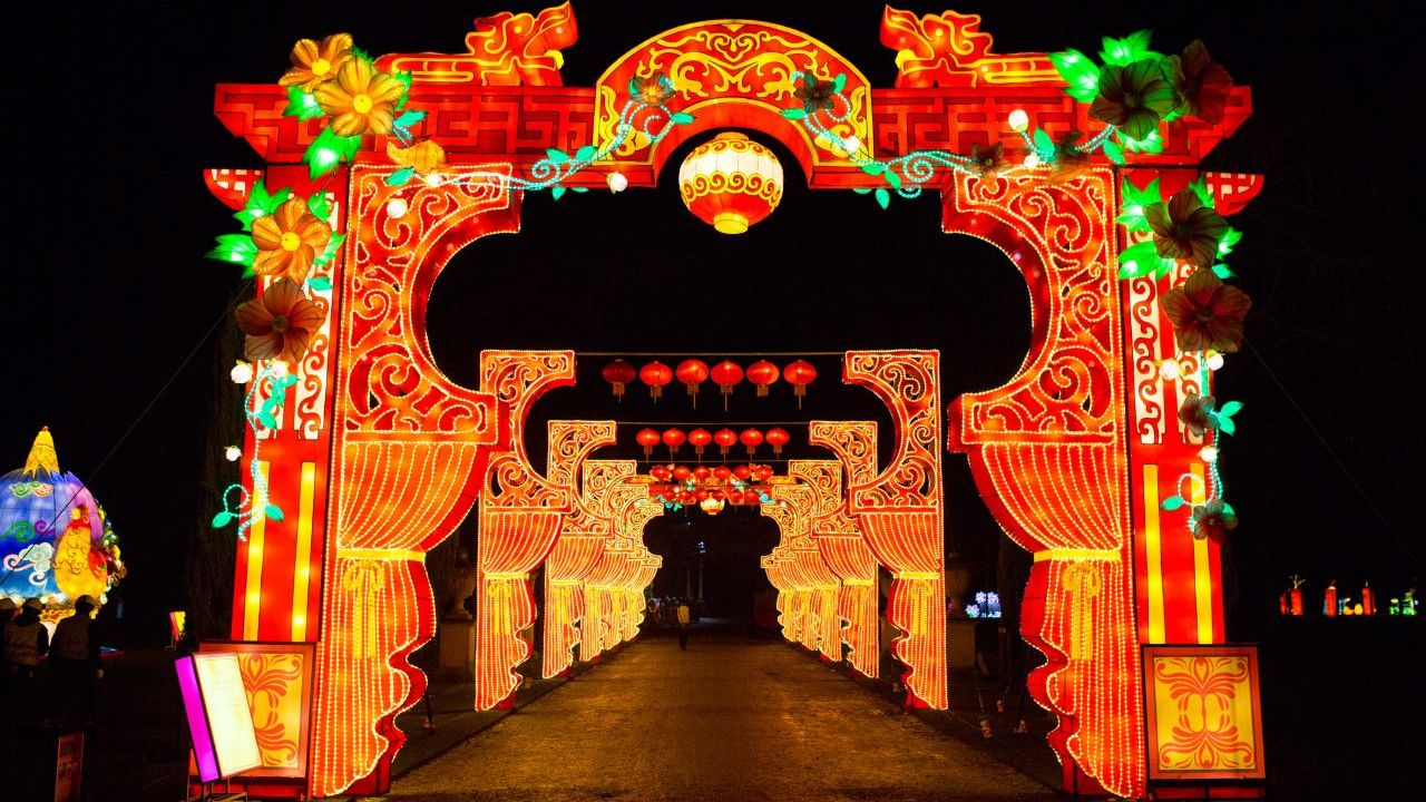 A park at night lit by illuminated red archways made from giant Chinese silk lanterns.