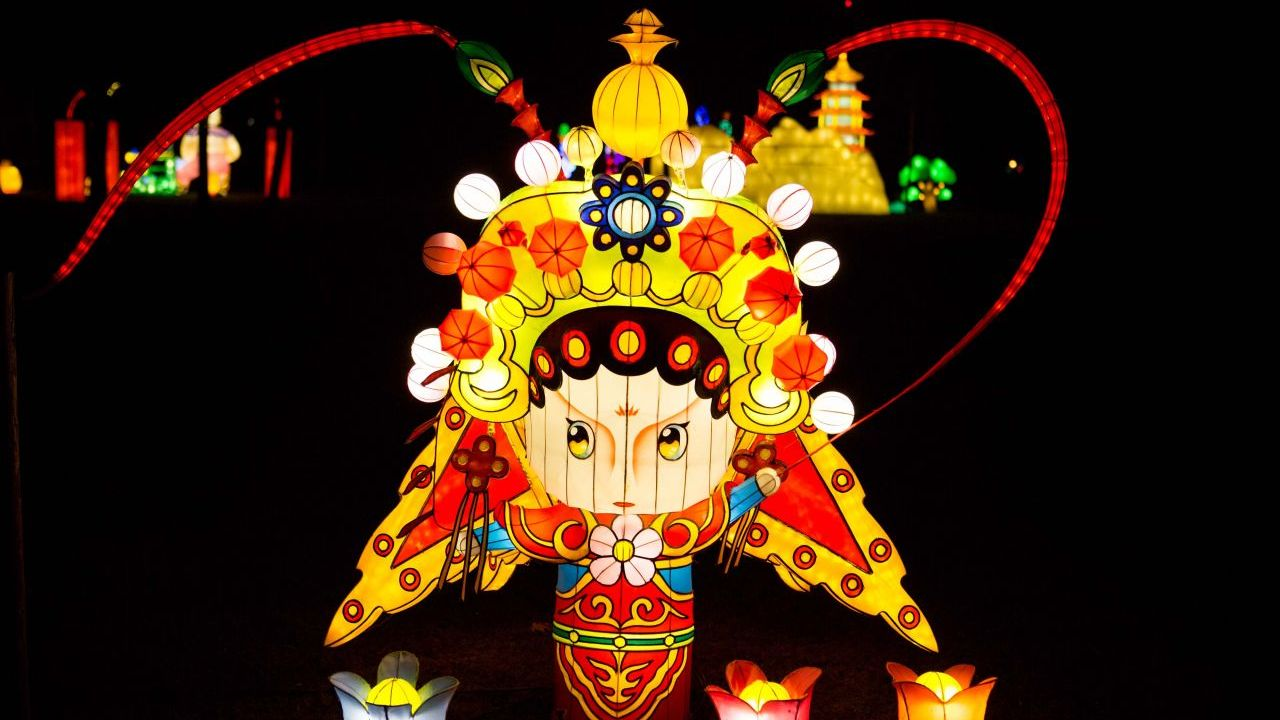 A park at night with a large decorative Chinese silk lantern in the shape of a cartoon Peking opera performer.