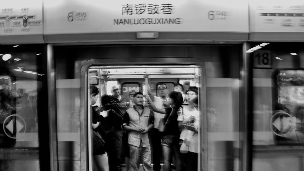 Black and white photo of a Beijing subway carriage with the doors open and people standing inside.