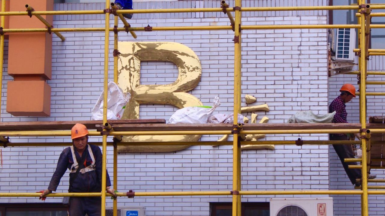 A tired-looking construction worker on scaffolding in front of a lavender coloured wall with a large gold letter B hanging on it