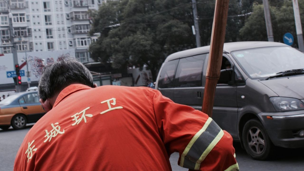 Close-up of a street-cleaner wearing an orange uniform with Chinese characters meaning 'Dongcheng Sanitation' written on it, against a backdrop of a city street.