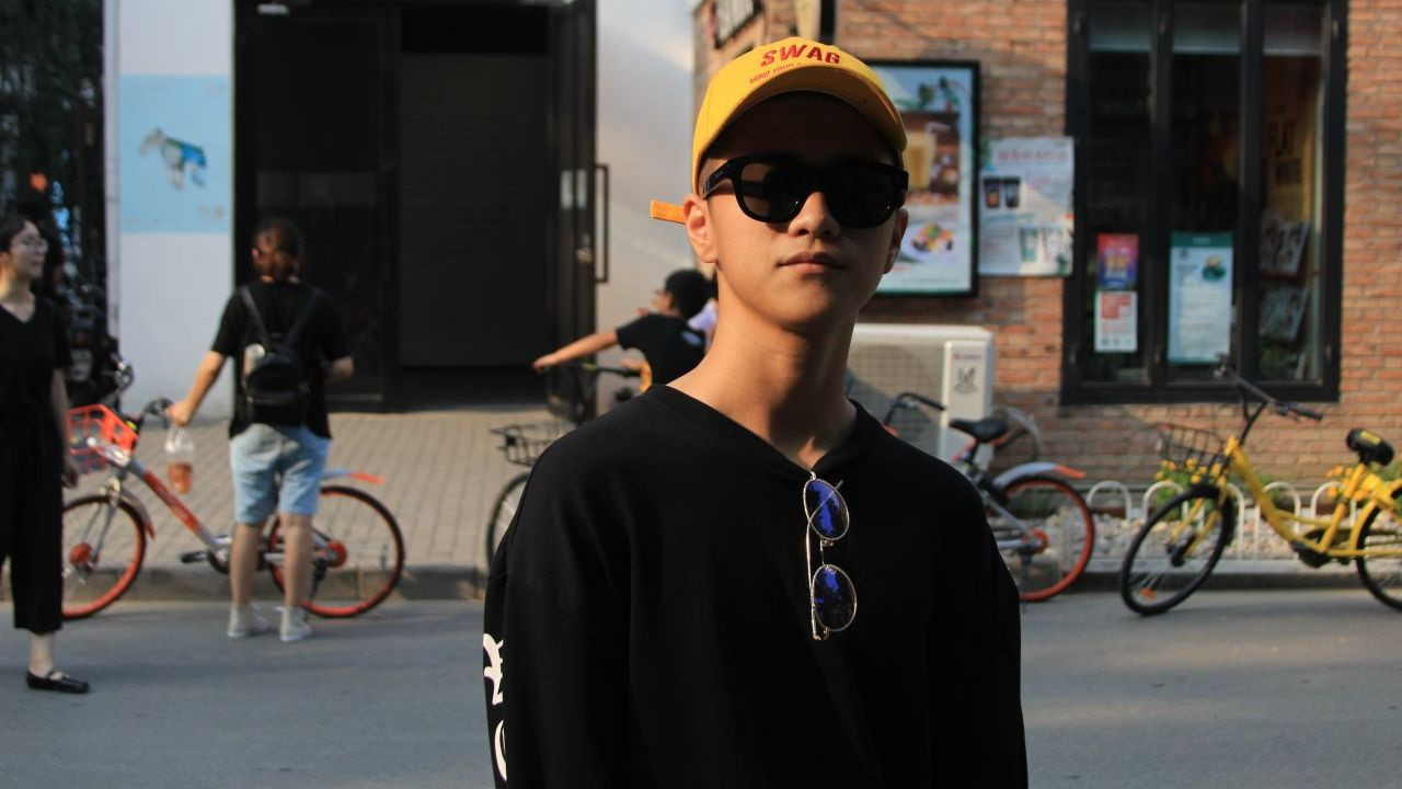 Photo of a young Chinese person wearing sunglasses and a yellow baseball cap with the word 'swag' printed on it, with a second pair of sunglasses around their neck, with a city street in the background.