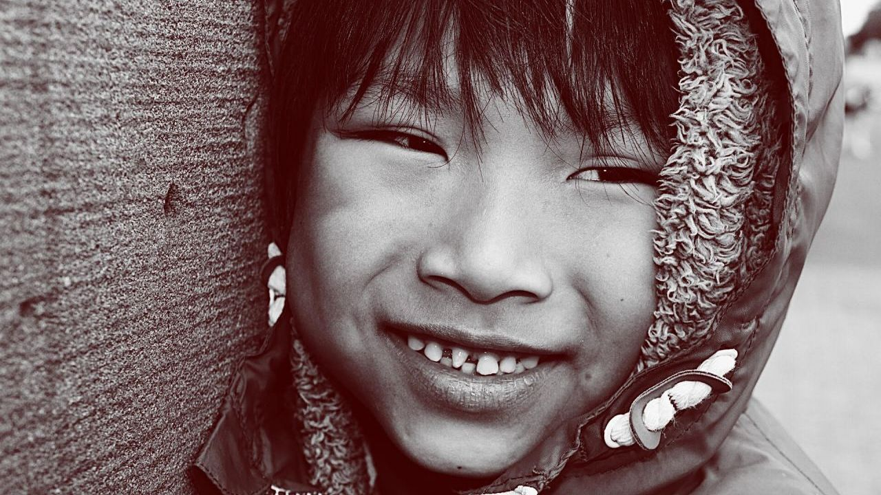 A black and white portrait of a child smiling wearing a hooded jacket standing next to a concrete wall.