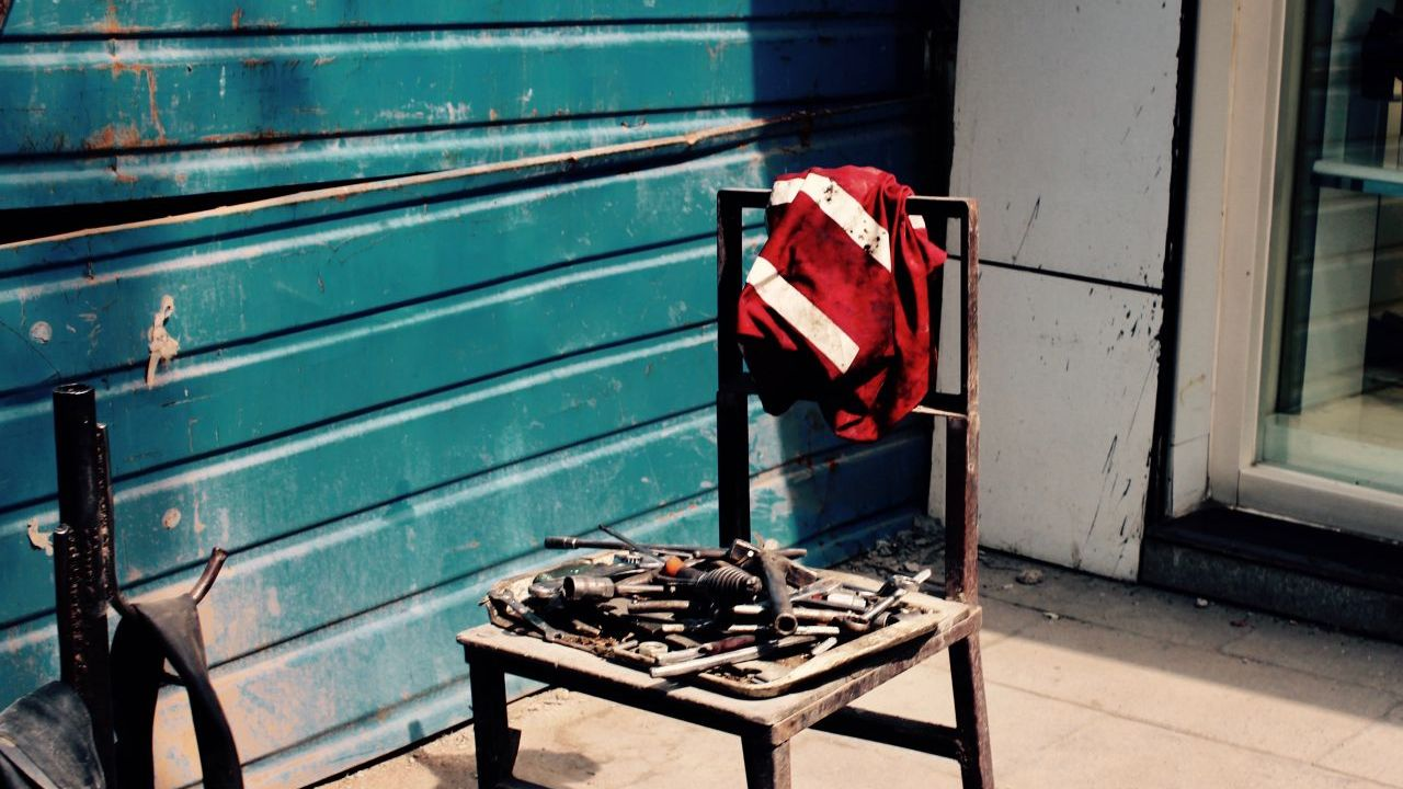 A high contrast photo of a red high-visibility jacket slung onto a broken wooden chair outside in front of a blue-green wall.