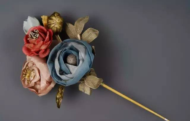 a silk velvet flower arrangement of three silk flower heads in blue, pink and red with large petals on a greenish-gold stem.