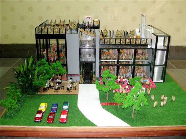 a diorama of a shopping mall featuring Beijing maohou 'hairy monkeys' inside, posed as if shopping and dining.