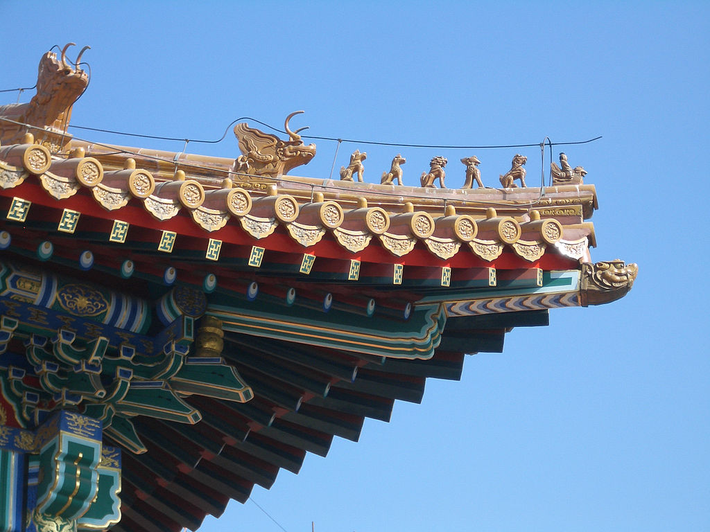 Closeup of a roof of an old building in the Forbidden City in Beijing, with yellow roof tiles and a line of 'roof beast' figurines along its eaves.