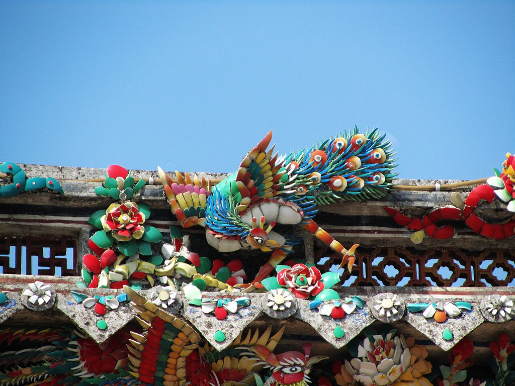 Closeup of a temple building with a colourful cut porcelain carving of birds and flowers.