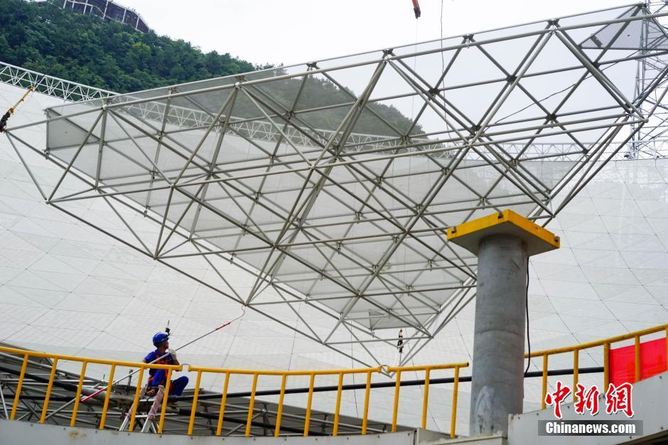 Placing one of the 4,600 panels during the construction of the FAST radio telescope in Guizhou Province, China.