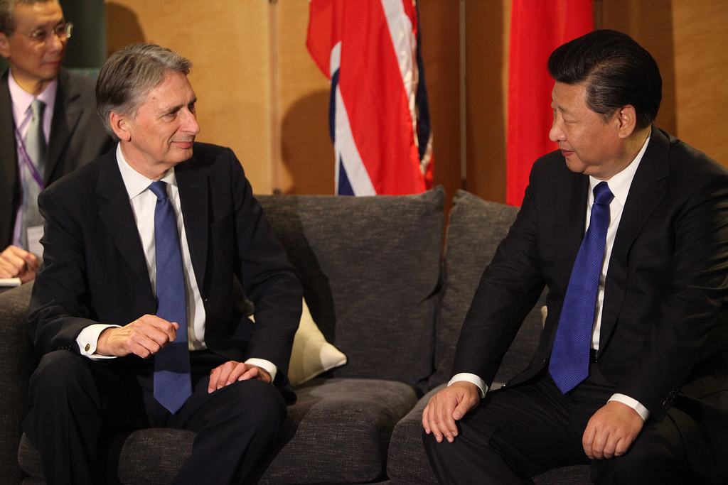 Politicians Philip Hammond and Xi Jinping sitting on a sofa talking at an official event.