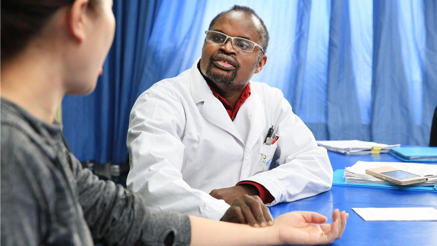 Diarra Boubacar, from Mali, takes the pulse of a patient at the traditional Chinese medicine hospital in the Xindu district of Chengdu in Southwest China's Sichuan province. Boubacar has been a TCM doctor for more than three decades.