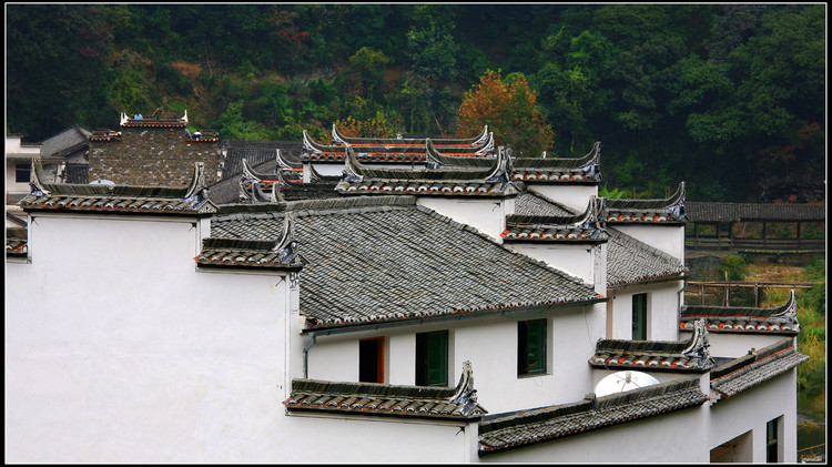 Grey slate roofs with 'horse head' features on white buildings in Hongcun.