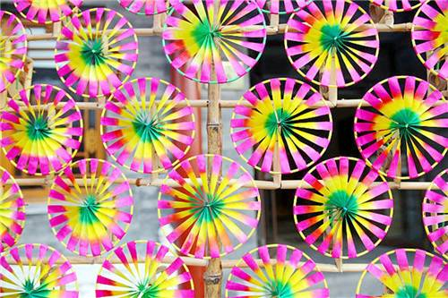 Pink, yellow and green pinwheels mounted on criss-crossing sticks.