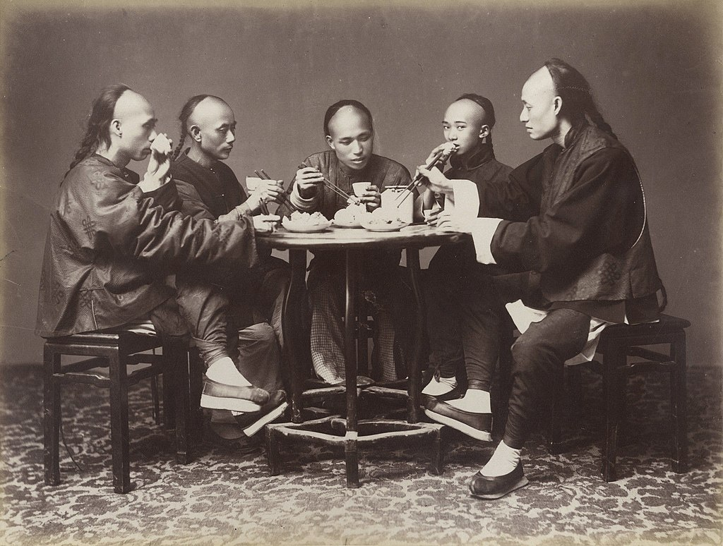 A black-and-white photograph of five men sitting around a table eating. All have their hair in the queue hairstyle, with a shaved front of the head and a long plait at the back of the head.