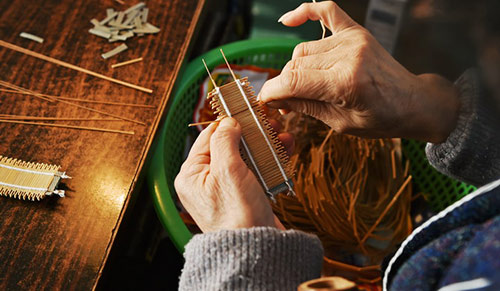 Close-up of the hands of a person making a comb, in the process of attaching the teeth of the comb in a weaving-like process.