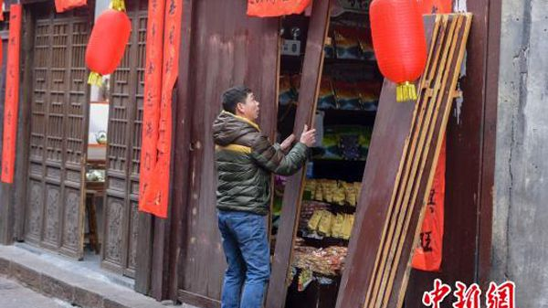 A shop owner in the ancient city of Fenghuang, Hunan Province opens his store for Spring Festival customers. Built in 1704, the city was added to the UNESCO World Heritage Tentative List in 2008.
