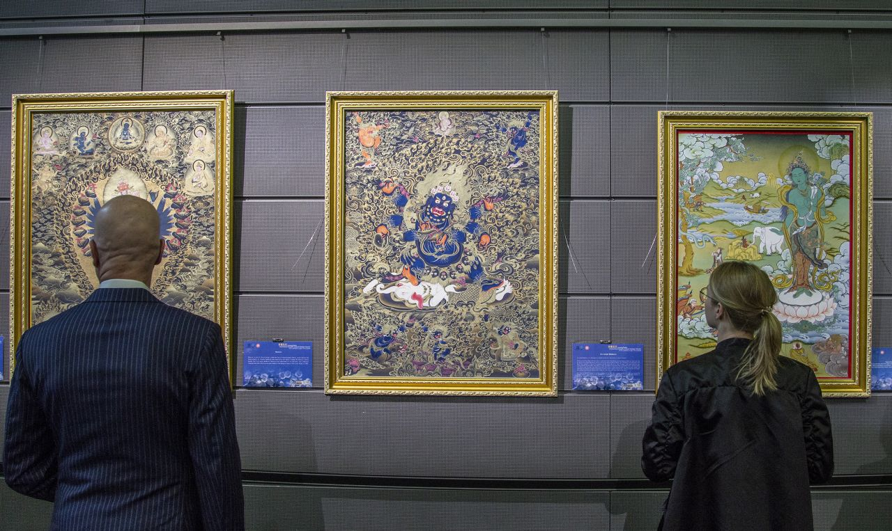 Visitors looking at Thangka-paintings at the Spotlight on Chinese Ink Painting exhibition at Musiikkitalo in Helsinki, Finland.