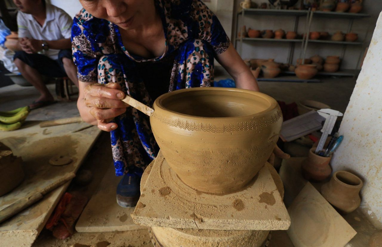 china yunnan province potter dai slow wheel technique decorating bamboo stick closeup