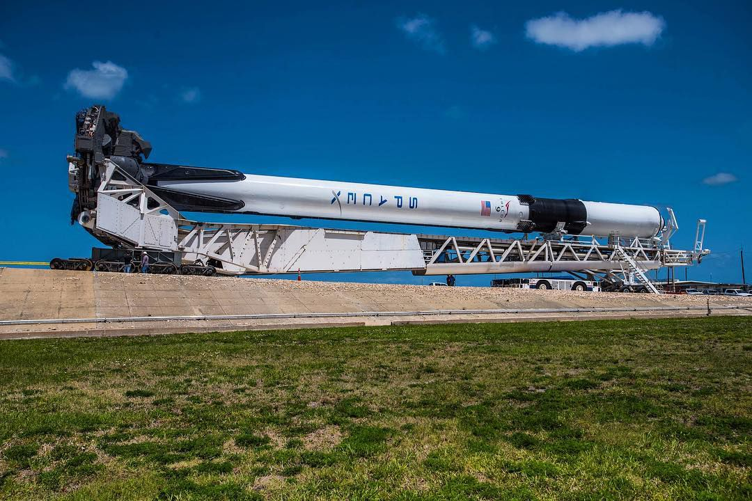 A SpaceX Falcon 9, with visible black landing legs and grid fins.