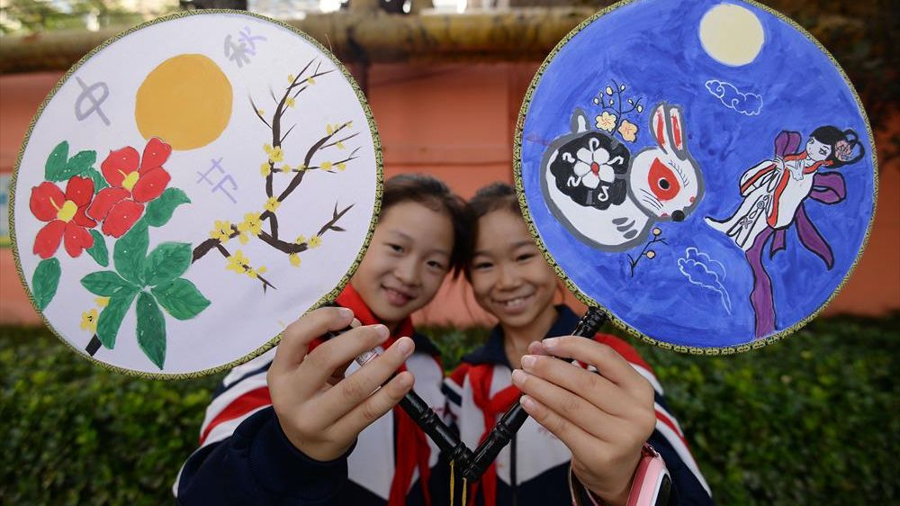 School children paint moon-shaped fans and experience traditional folk culture to celebrate the Mid-Autumn Festival in Handan, Hebei Province.