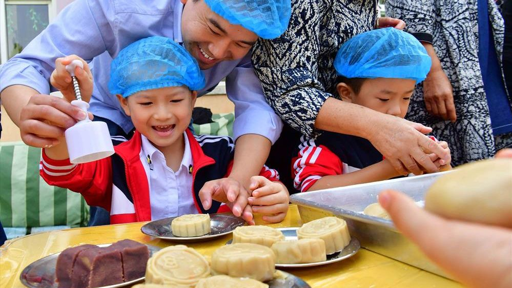 Children in Puyang, Henan Province, make mooncakes with their fathers, who have returned home from their jobs in neighbouring provinces and abroad.