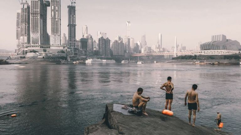 Swimmers on the riverside opposite the construction of Raffles City Chongqing, southwest China. Photographer: Zhu Wenqiao - one of the 20 shortlisted entries for the Architectural Photography Awards 2018.