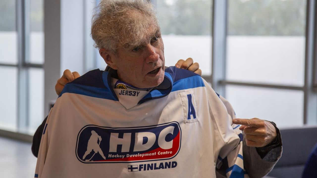 Director and cinematographer Christopher Doyle posing with an ice hockey jersey.