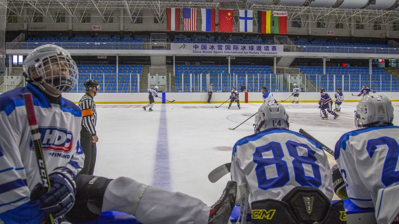 Finnish players on the bench watching Finland play ice hockey against the US.