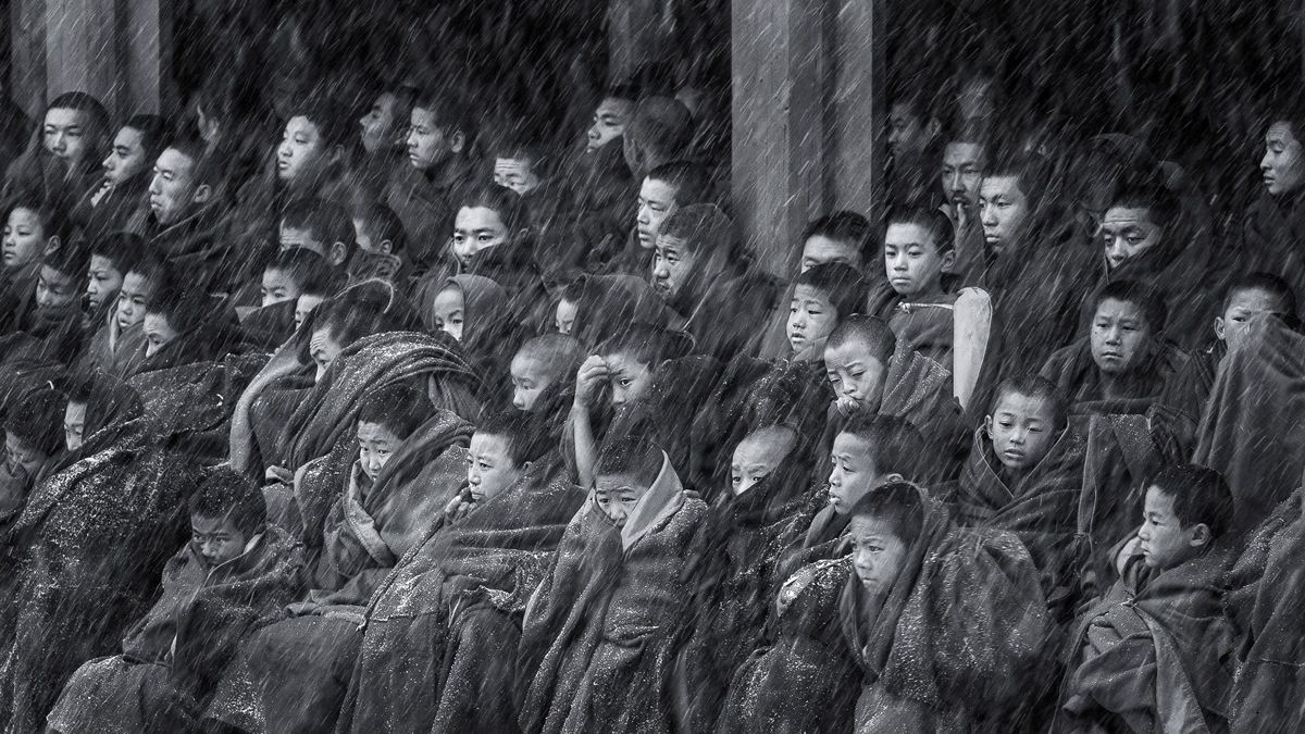 "Chinese photographer Rong Qingjun received an honourable mention in the Fascinating faces and characters category at the 2018 Siena International Photo Awards for the photo ""Young Lama in the Snowstorm"". The photo was taken at the Gerdeng temple in east C"