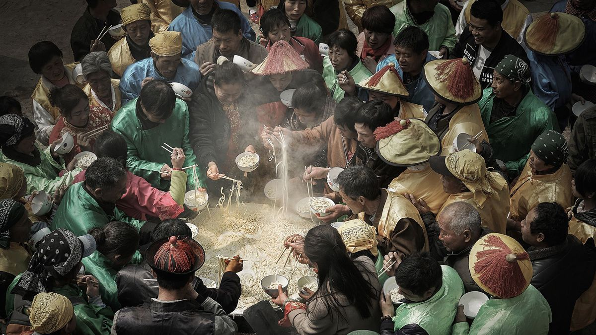 "Chinese photographer Liao Jianhui received a remarkable award in the Journeys & Adventures category at the 2018 Siena International Photo Awards for the photo ""Big Pot Noodles""."