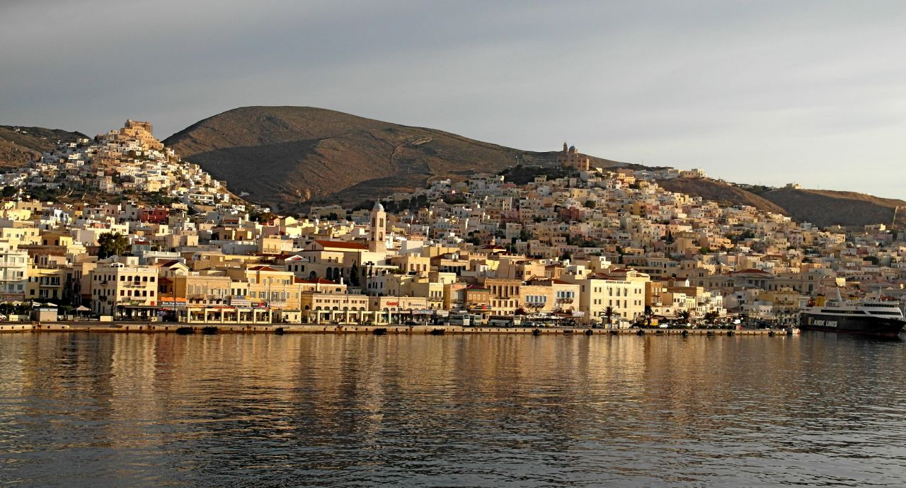 Panoramic view of Ermoupolis port city, with its picturesque hills. The one on the left is the Catholic one with St George's Cathedral visible at the top, whereas on the right one's top, lies the Orthodox Church of Anastasi.