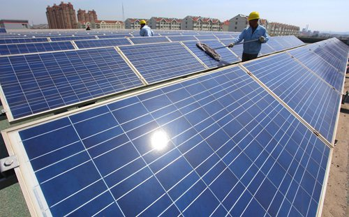 Workers clean up rooftop solar panels to prepare for the coming summer, a peak season for electricity consumption, in Jimo, Shandong Province, on May 12.