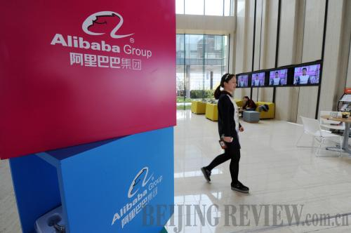 A staff member from Alibaba Group passes by the group's logo at its Hangzhou headquarters.