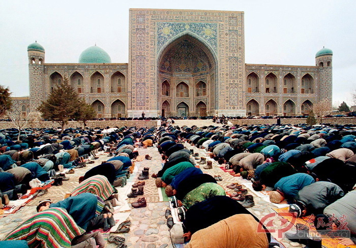 Uzbek Muslims pray in front of the Registan complex of several mosques in Samarkand, an ancient city of Central Asia. As a major hub along the Silk Road, it connected three great empires – Persia, India, and China.