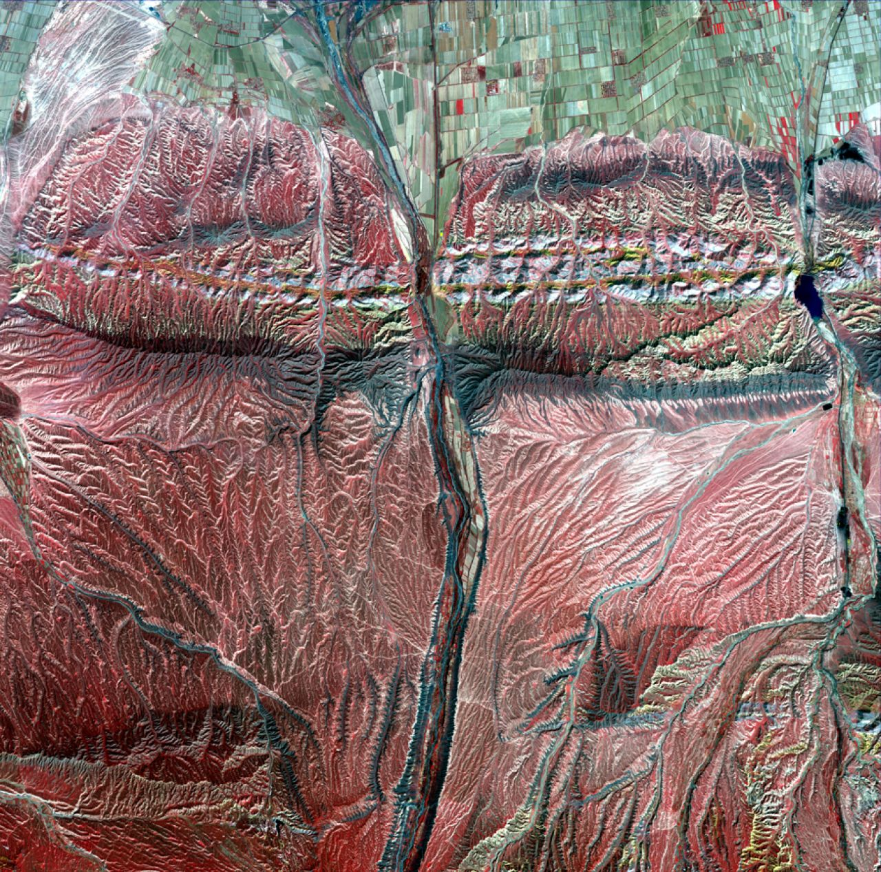 """""""Muscles"""" of the Changji Hutubi Valley. Taken on April 20, 2014, green farmland is seen above with mountains (red) worn by water erosion below."""