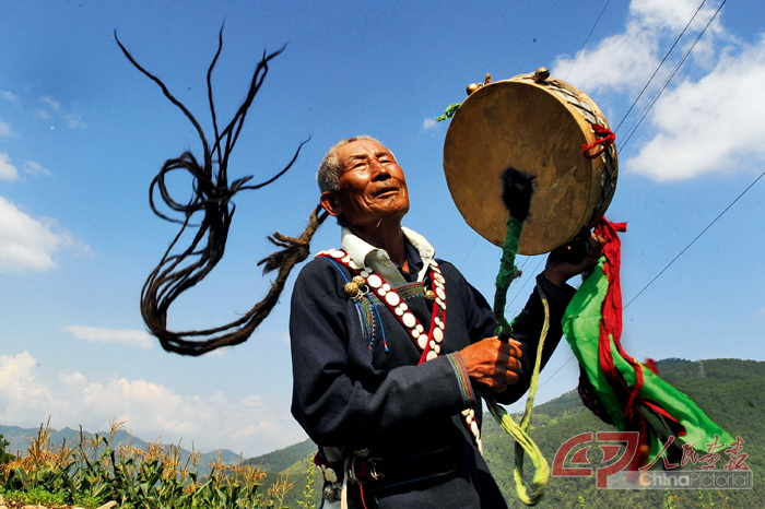 A Yi priest performs a ritual at a local tourism festival, Xichang.