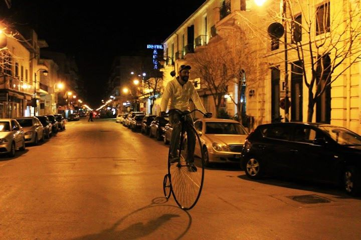 Vangelis riding an old-fashioned penny farthing bicycle.